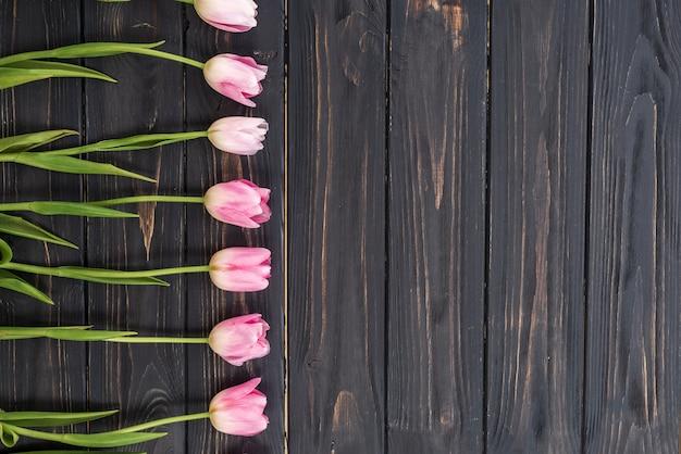 Rosa tulpenbündel auf hölzernem plankenhintergrund der dunklen scheune.