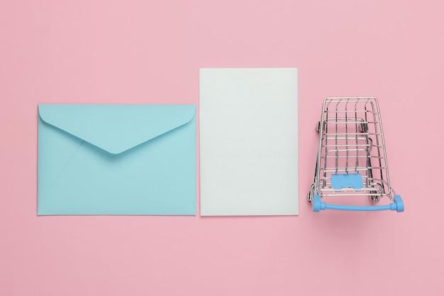 Rosa umschlag mit brief und einkaufswagen auf rosa pastellhintergrund. modell für valentinstag, hochzeit oder geburtstag. draufsicht