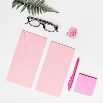 Rosa umschlag; papier; haftnotiz; stift; büroklammern; brillen und farn auf weißem hintergrund