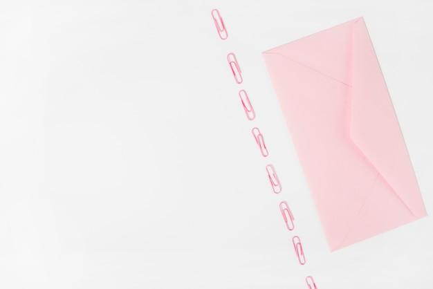 Rosa umschlag und büroklammern auf weißem hintergrund