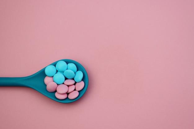 Rosa und blaue süße tropfen in einem blauen löffel auf einem hellrosa hintergrund Premium Fotos