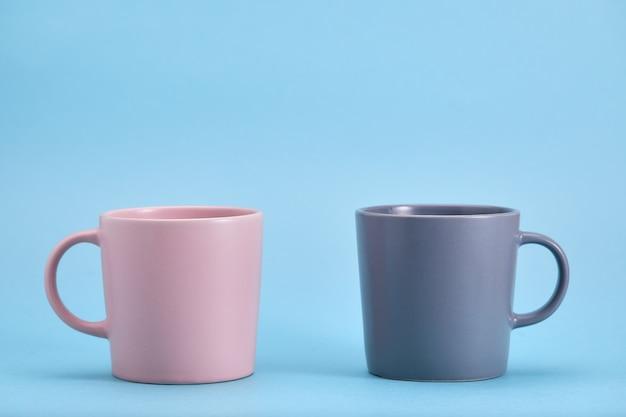 Rosa und blaue tasse auf einem blauen raum. der kampf der gegensätze, das spiel der farben.