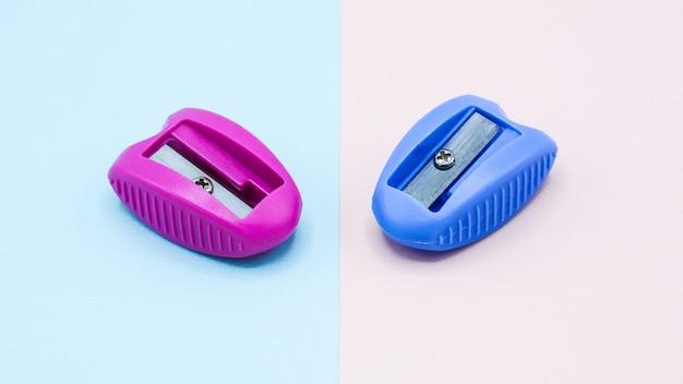 Rosa und blauer plastikbleistiftspitzer auf rosa und blauem hintergrund