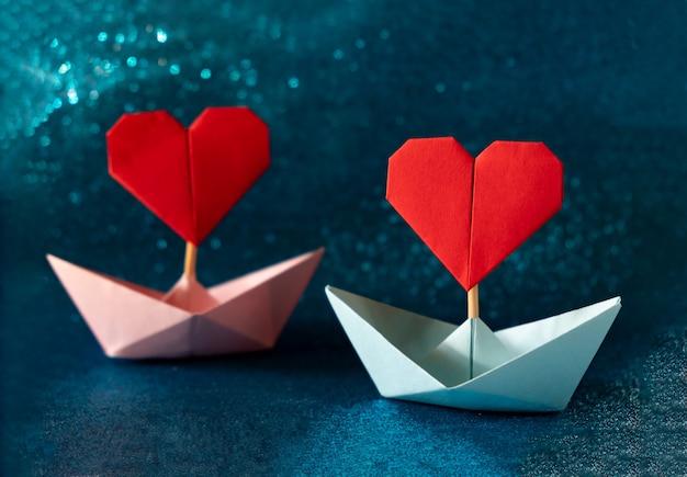 Rosa und blaues papierboot auf glitzerndem blauem hintergrund. romantisches valentinstagskonzept mit platz für text.