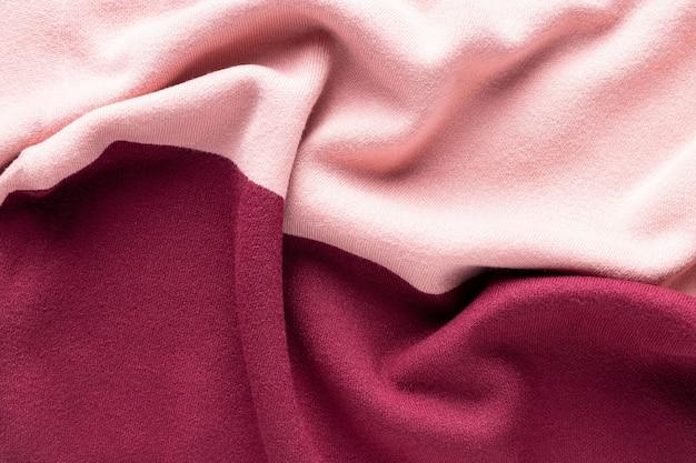 Rosa und burgunderfarbene strickstruktur mit falten. mode strickwaren