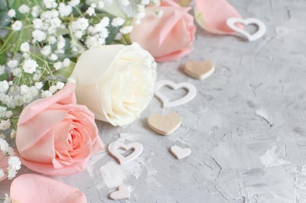 Rosa und cremefarbene rosen mit herzen auf grauem hintergrund