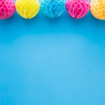 Rosa und gelbe bienenwabe pom-pom-papierballdekoration auf blauem hintergrund