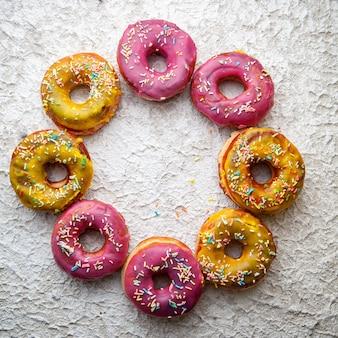 Rosa und gelbe donuts in einer kreisform auf einem weißen strukturierten hintergrund. draufsicht.