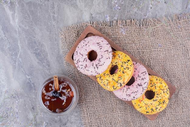 Rosa und gelbe donuts mit einer tasse glitzern