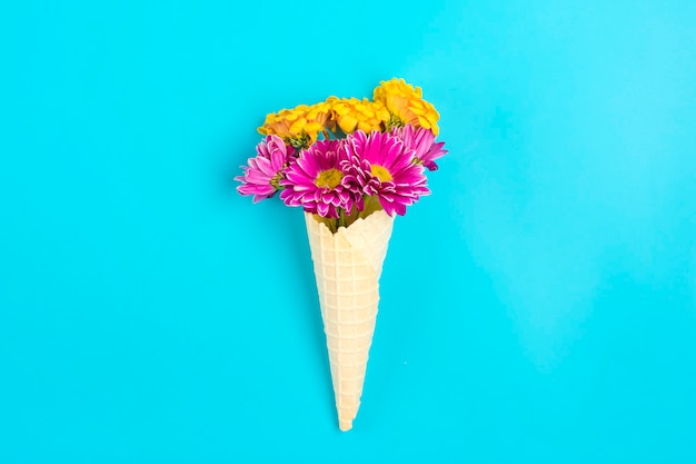 Rosa und gelbe frühlingsblumen gänseblümchen in eiscreme-waffelkegel auf blauem hintergrund
