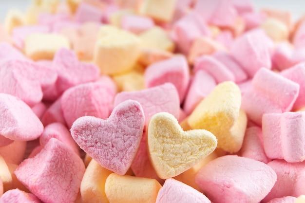Rosa und gelbe herzform-mini-marshmallows-texturen. marshmallows food hintergrund mit kopierraum