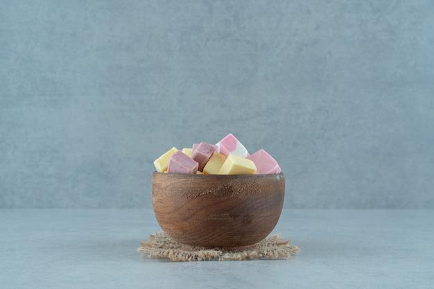 Rosa und gelbe marshmallow-bonbons in einer holzschale auf weißer oberfläche