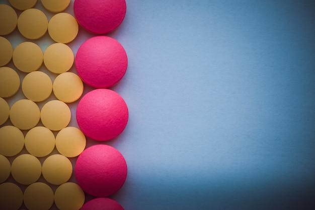 Rosa und gelbe pillen in folge auf einem blauen hintergrund.