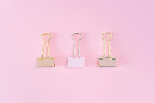 Rosa und goldene büroklammern auf einem pastellrosahintergrund.