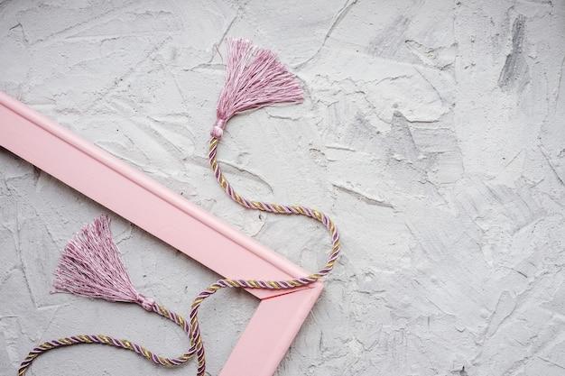 Rosa und goldene spitze für vorhänge mit quasten auf einem grauen gipshintergrund und einem leeren rahmen. zubehör für den innenraum.