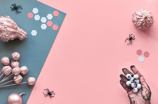 Rosa und graue geteilte papierwand mit spinnen und glänzend bemalten dekorativen kürbissen in rosa und grauen farben