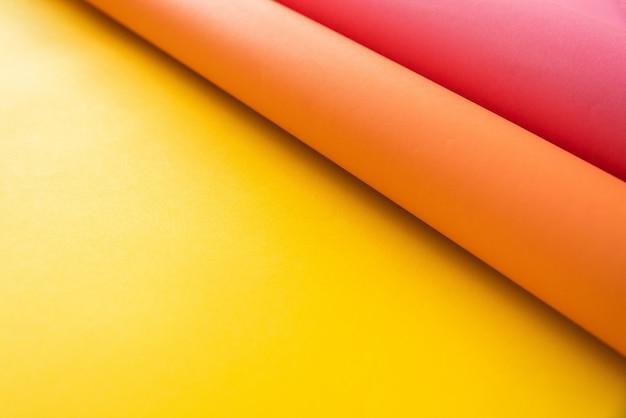 Rosa und orange papiere, die zusammen über gelbes farbpapier in der abstrakten form verbiegen. abstrakter farbpapierhintergrund mit kopienraum.
