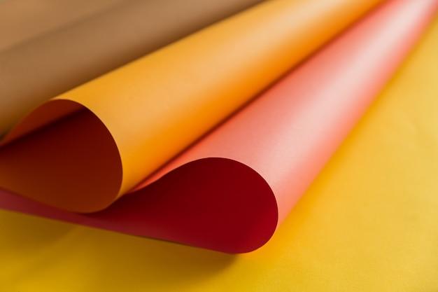 Rosa und orange papiere, die zusammen über gelbes farbpapier in der abstrakten form verbiegen. abstrakter farbpapierhintergrund.