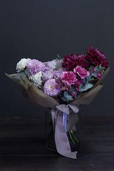 Rosa und purpurroter getonter blumenstrauß in der weinleseart auf dunkelheit