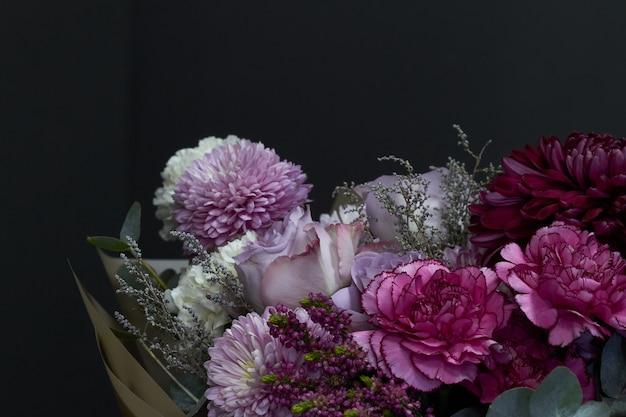 Rosa und purpurroter getonter blumenstrauß in der weinleseart auf einem dunklen hintergrund