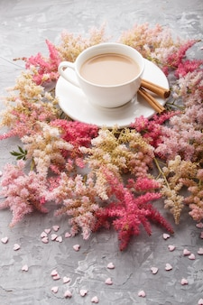 Rosa und rote astilbe-blumen und ein tasse kaffee auf einem grauen konkreten hintergrund