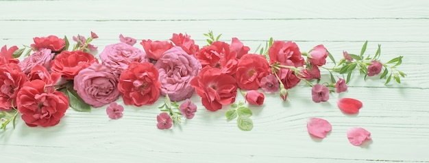 Rosa und rote rosen auf grünem holzuntergrund