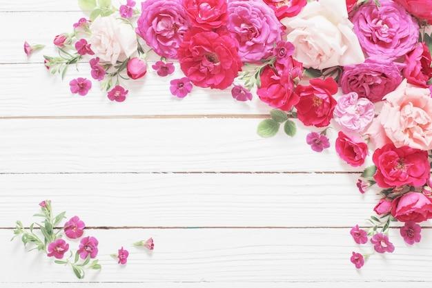 Rosa und rote rosen auf weißem holzuntergrund