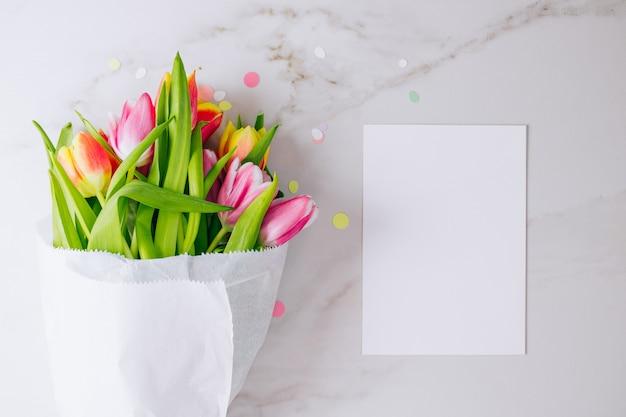Rosa und rote tulpen mit weißem sauberem leerzeichen für ihren text auf marmorhintergrund