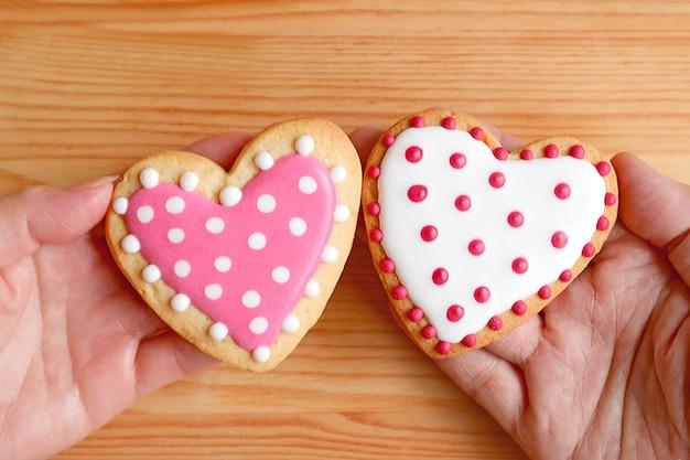 Rosa und weiß gepunktete herzförmige kekse in den händen des paares zusammengesetzt
