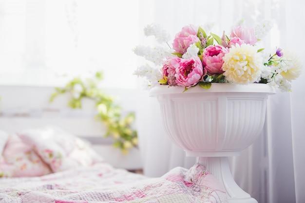 Rosa und weiße blumen in einer vase nahe dem bett