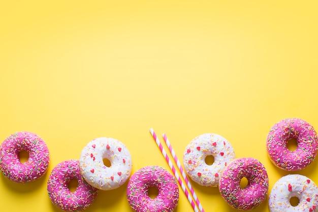 Rosa und weiße donuts mit feierartikel auf gelb