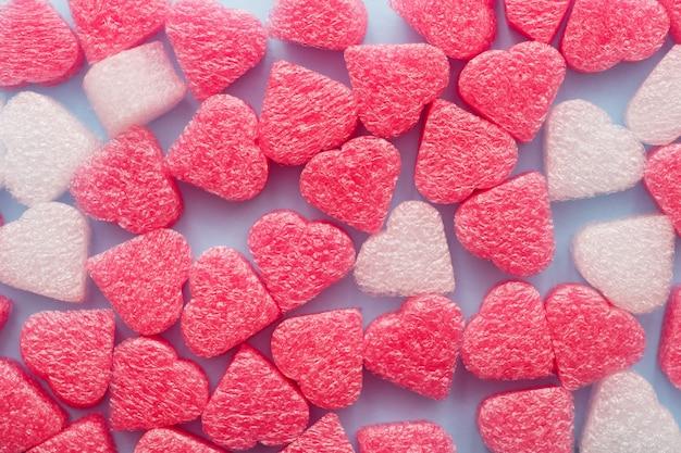 Rosa und weiße herzkonfettis nah oben auf blauem pastell. valentinstag oder muttertag