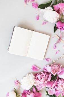 Rosa und weiße pfingstrosen mit einem notizbuch auf grau