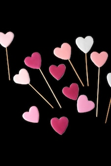 Rosa und weiße plätzchen auf einem stock in form der herzen auf einem schwarzen lokalisiert. valentinstag.