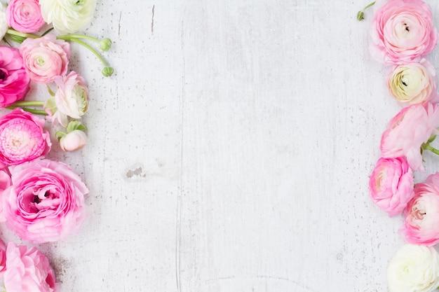 Rosa und weiße ranunkelblumen auf der flachen laienszene des weißen hölzernen hintergrunds