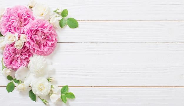 Rosa und weiße rosen auf weißem hölzernem hintergrund