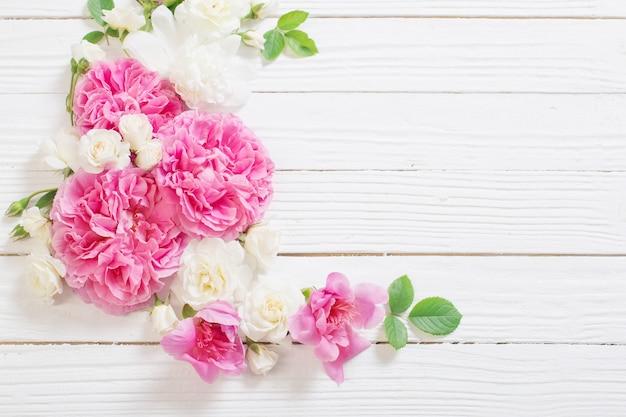 Rosa und weiße rosen auf weißer holzoberfläche