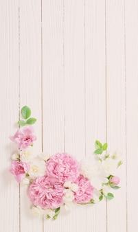 Rosa und weiße rosen auf weißer holzwand
