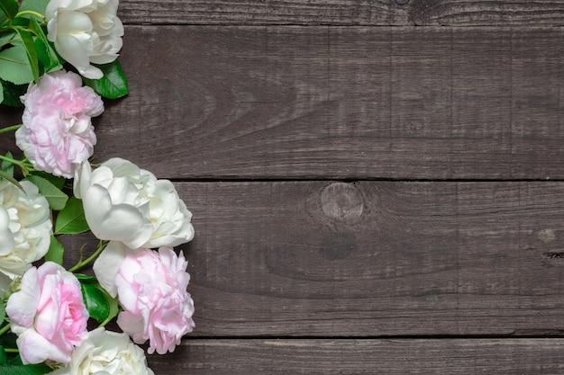 Rosa und weiße rosen blühen über rustikalem holztisch