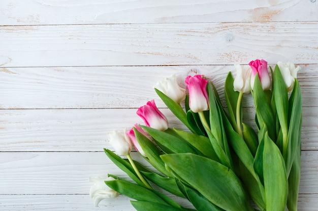 Rosa und weiße tulpen auf weißem hölzernem hintergrund. speicherplatz kopieren