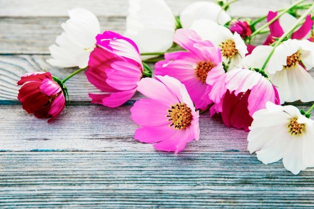 Rosa und weißer sommerblumenstrauß auf grauem hölzernem hintergrund