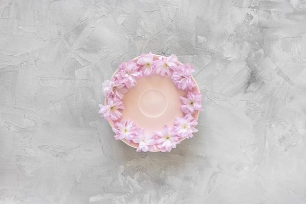 Rosa untertasse und frische frühlings-sakura-blumen