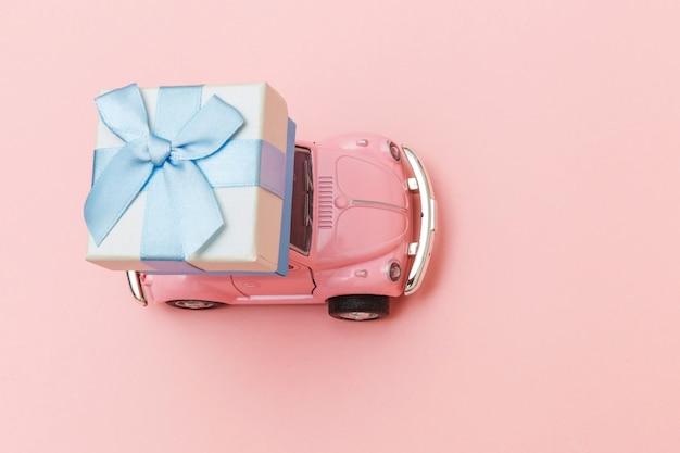 Rosa vintage retro spielzeugauto, das geschenkbox auf dach lokalisiert auf rosa tisch liefert