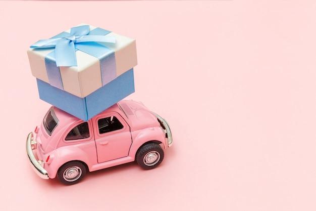 Rosa vintage retro-spielzeugauto, das geschenkbox auf dach lokalisiert auf trendigem pastellrosa hintergrund liefert