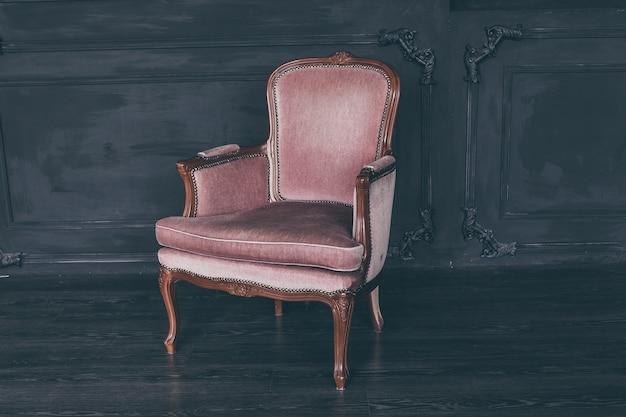 Rosa vintage-sessel in einem dunklen loft-raum