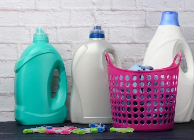 Rosa wäschekorb und plastikflaschen mit flüssigwaschmittel auf weißem backsteinmauerhintergrund