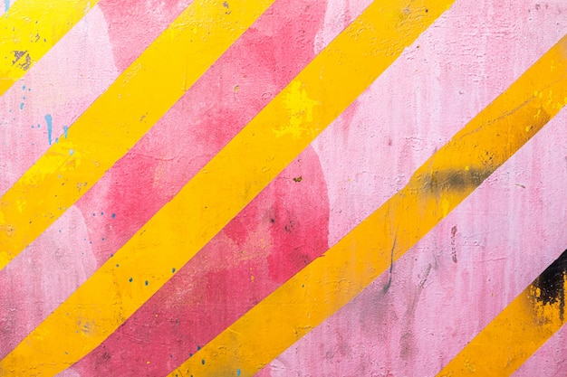 Rosa wand mit gelben diagonalen streifen, textur grunge hintergrund. geometrische bunte wand