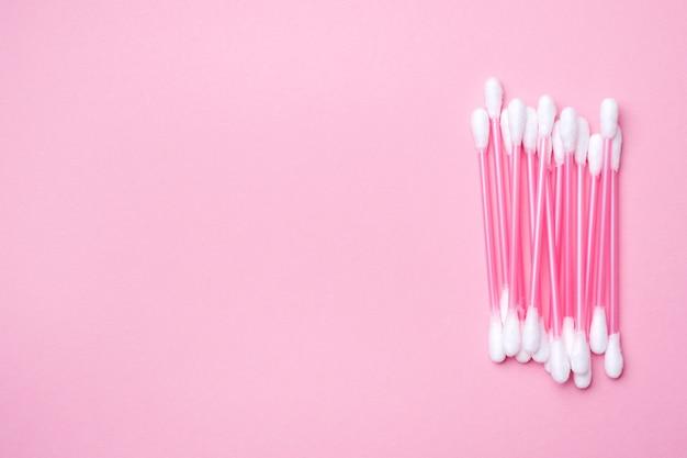 Rosa wattestäbchen auf rosa. hintergrund mit exemplar