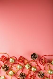 Rosa weihnachts- oder neujahrshintergrund mit roten und goldenen verzierungen für weihnachtsbaum mit freiem raum. der blick von oben. neujahrsstimmung.