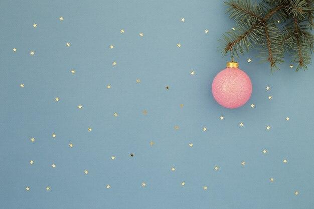 Rosa weihnachtskugel und grüner zweig